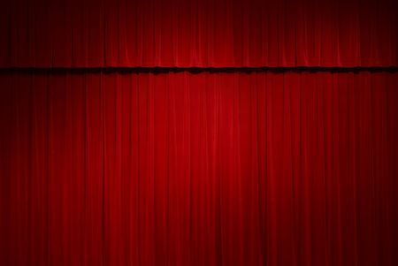 closed red stage curtains with a spot light on them photo
