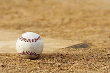 outfield: one baseball on home plate at a sports field