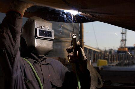 a welder working at shipyard under vessel Reklamní fotografie