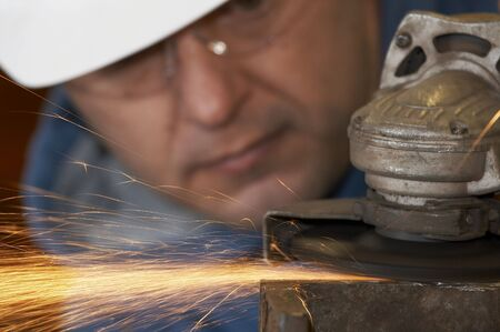 a picture of a worker grinding steel
