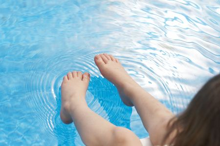 a young kids feet over blue pool water