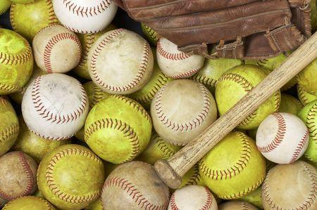 a picture of baseballs, softballs, a bat and glove 写真素材