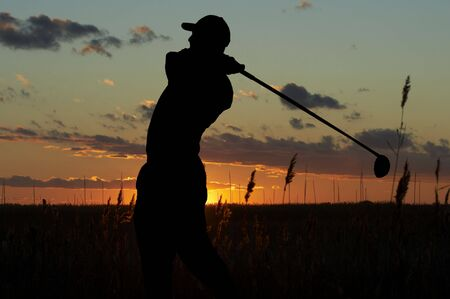 a silhouette of a golfer on a mourning sunset Imagens
