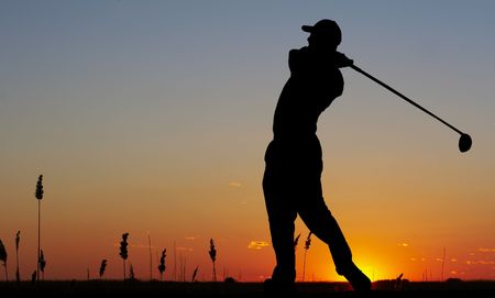 a silhouette of a golfer on a bright sky photo