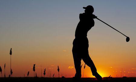 a silhouette of a golfer on a bright sky
