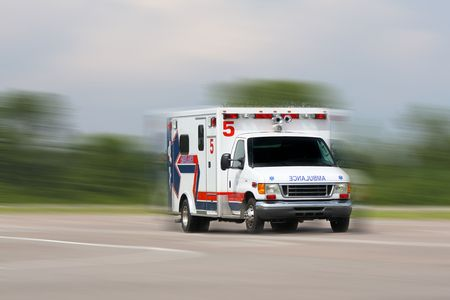 ambulance in motion driving down road photo