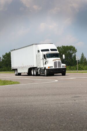 shipping truck driving down road on blue sky Stock Photo