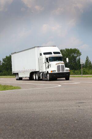 shipping truck driving down road on blue sky 版權商用圖片