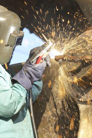 worker arcing a strap off of a tug boat wheel Reklamní fotografie
