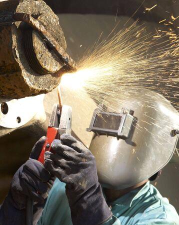 an arc welder working on a tug boat wheel