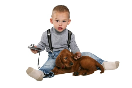 The boy siting with a puppy and the camera on a white background photo