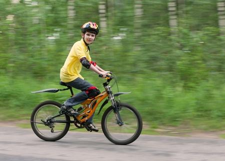 safety helmet: Chico joven montando r�pidamente en una bicicleta de monta�a usando casco de seguridad de protecci�n y rodilleras y coderas. Toma de fotograf�as con la panor�mica. Foto de archivo