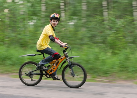 Young boy riding fast on a mountain bike wearing protective safety helmet and knee and elbow pads. Shooting with panning.