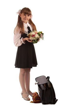 Cute young girl in uniform standing with flowers; isolated on white background photo