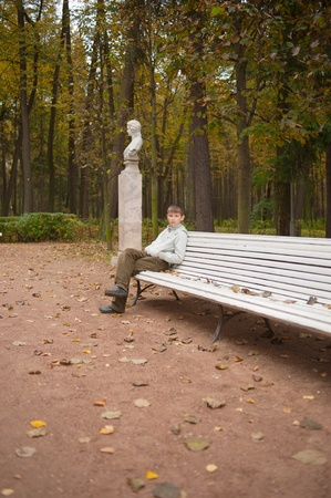 The teen sits on bench in autumn park, vertical photo