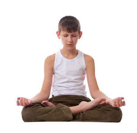 Boy sitting on floor meditating. Yoga. Lotus Position.  Imagens