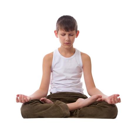 Boy sitting on floor meditating. Yoga. Lotus Position.  Standard-Bild
