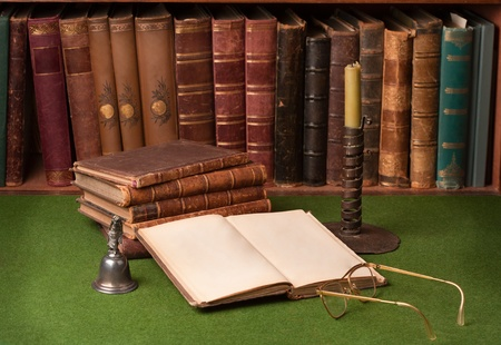 Antique leather books, tin candlestick and reading glasses on green blotter. Imagens