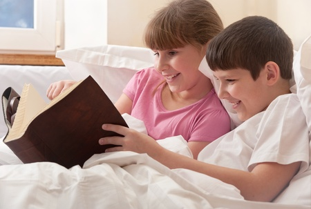 child in bed: brother and sister, reading book, in bed, close up