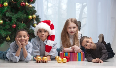 decorating christmas tree: Happy children holding Christmas gifts and sitting on the floor