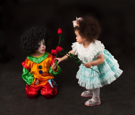 little girl gives flowers to the boy - clown, black Stock Photo - 13758611