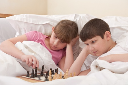 brother and sister play chess in bed, indoors photo