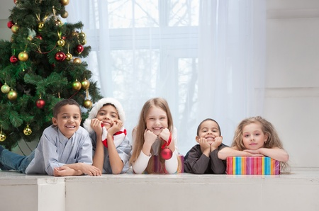 Happy children holding Christmas gifts and sitting on the floor Stock Photo - 15379858