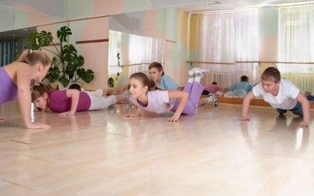 educacion fisica: grupo de ni�os que participan en el entrenamiento f�sico en el gimnasio. Horizontal.