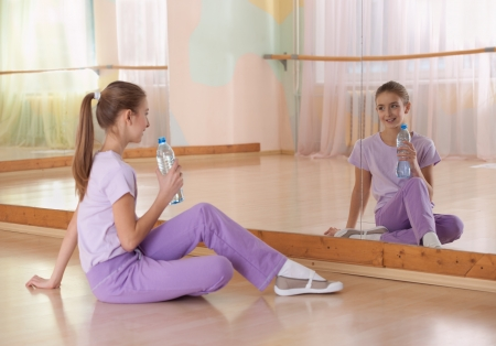 elementary age girl: Girl in sportswear with bottle of water sits on the field at the gym in the mirror. Horizontal.