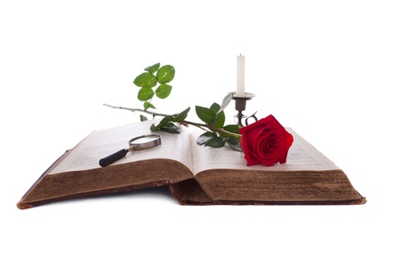 Open book with a red rose, a magnifying glass and a candle. Antique Bible. Isolated on white. photo