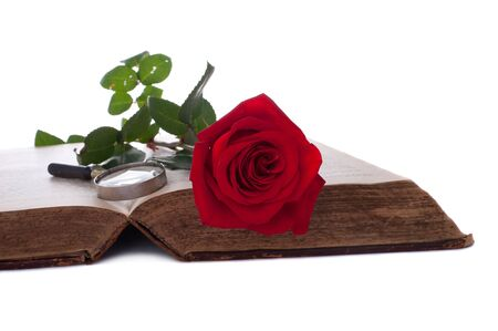 Open book with red rose and magnifying glass. Antique Bible. Isolated on white. photo