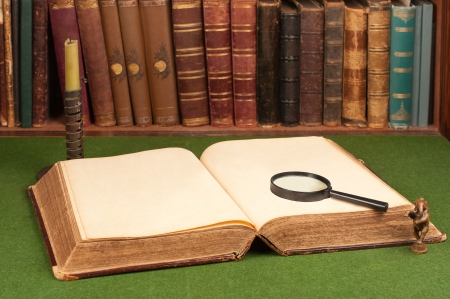 literary: Antique leather books, tin candlestick and magnifying glass on green blotter.