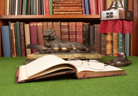 blotter: Antique leather books, lamp and reading glasses on green blotter.