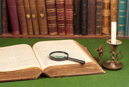 Antique leather books, tin candlestick and magnifying glass on green blotter. photo