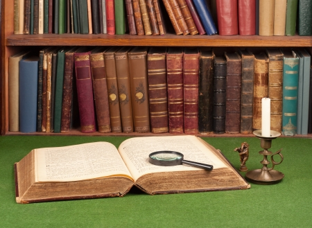 Antique leather books, tin candlestick and magnifying glass on green blotter.