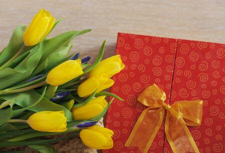 Spring yellow tulips and gift lying on wood photo