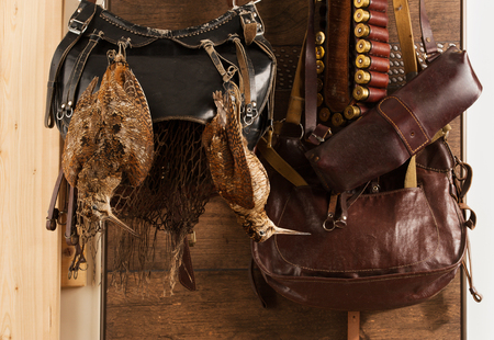 Hunting trophies and equipment hang on wall. Hunting of woodcock birds. Horizontal.