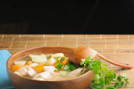 Light summer dietary cold soup with fish, vegetables and leeks in wooden bowl Stock Photo