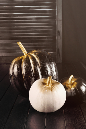 Black and white pumpkins. Home decoration for Halloween in the modern style. Vertical.