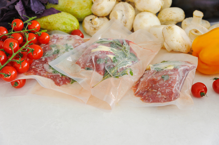 Three raw steaks in vacuum package, vegetables and mushroom. Sous-vide, new technology cuisine. Horizontal.