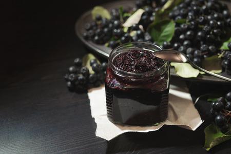 Dżem z czarnej aronii ( Aronia melanocarpa ) i jej jagód na ciemnym stole. Domowe przetwory. Poziomy. Zdjęcie Seryjne
