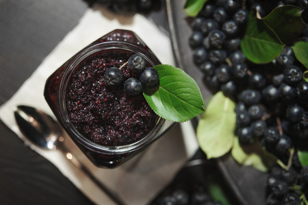 Jam from black chokeberries ( Aronia melanocarpa ) and its berries on dark table. Homemade preserves. Top view. Horizontal.