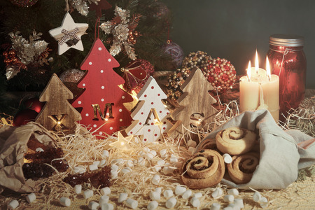Four decorative wooden Christmas trees with carved letters xmas and christmas sweets. Christmas family traditions. 免版税图像