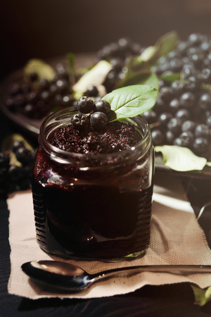 Jam from black chokeberries ( Aronia melanocarpa ) and its berries on dark table. Homemade preserves. Vertical.