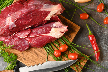 Fresh dark meat with ingredients for cooking on brown wooden cutting board. Hunting composition. Wildanimal hunting. Standard-Bild - 113886189