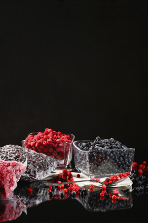 Frozen raspberry and blueberry berries in glass bowls on a dark background. Stock Photo