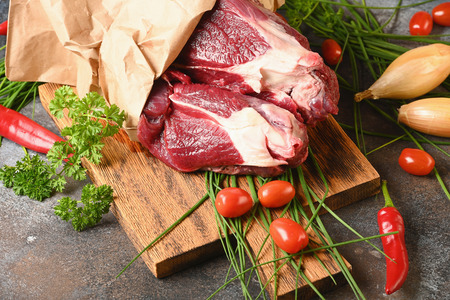 Fresh dark meat with ingredients for cooking on brown wooden cutting board. Hunting composition. Wildanimal hunting.