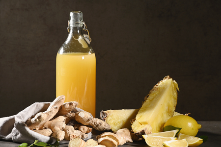 Bottle of homemade pineapple juice with ginger, lemon and ingredients. Horizontal.