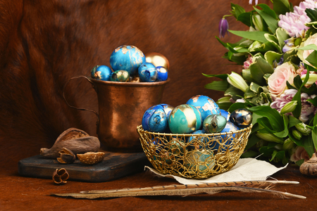Painted colored Easter eggs in golden bowl and copper mug near bouquet of flowers on red animal skin. Boho stile.