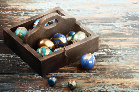 Painted colored Easter eggs in dark wooden box on dark wooden background. Boho stile. Archivio Fotografico